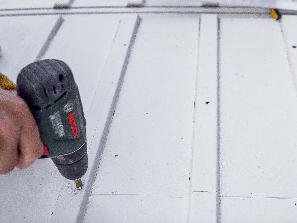 Gat boren in het dak van de camper met een boormachine